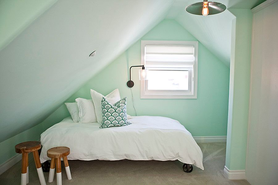 Tiny attic bedroom in pastel green also serves as a great guest room when needed