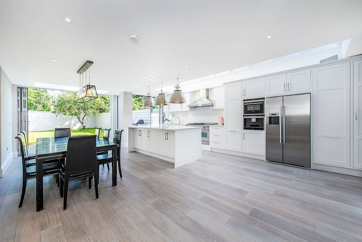 Transitional style kitchen with gorgeous wooden floor, ample naural lighting and dining space