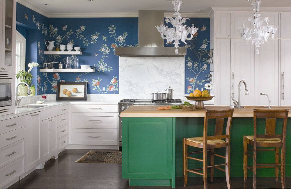Wallpaper in blue with flowery pattern feels natural in this eclectic kitchen with smart green island