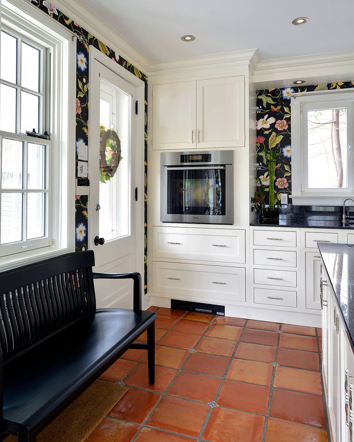 Wallpaper with flower pattern brings color and contrast to the kitchen in white