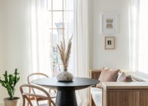 Wooden-bench-adds-additional-setaing-space-to-the-small-dining-area-with-black-round-dining-table-82152-217x155