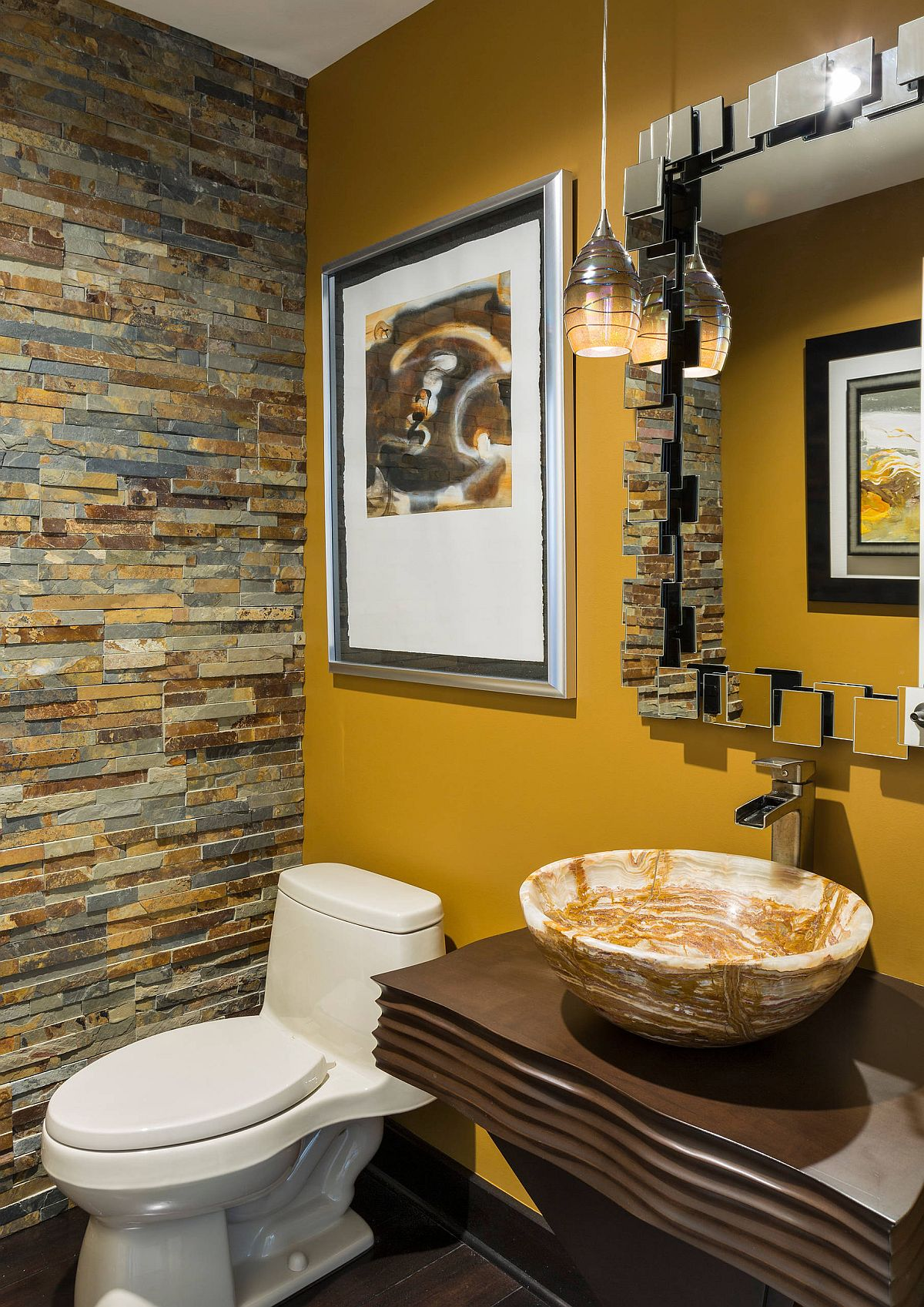 Yellow accent wall in the tiny powder room brightens the setting