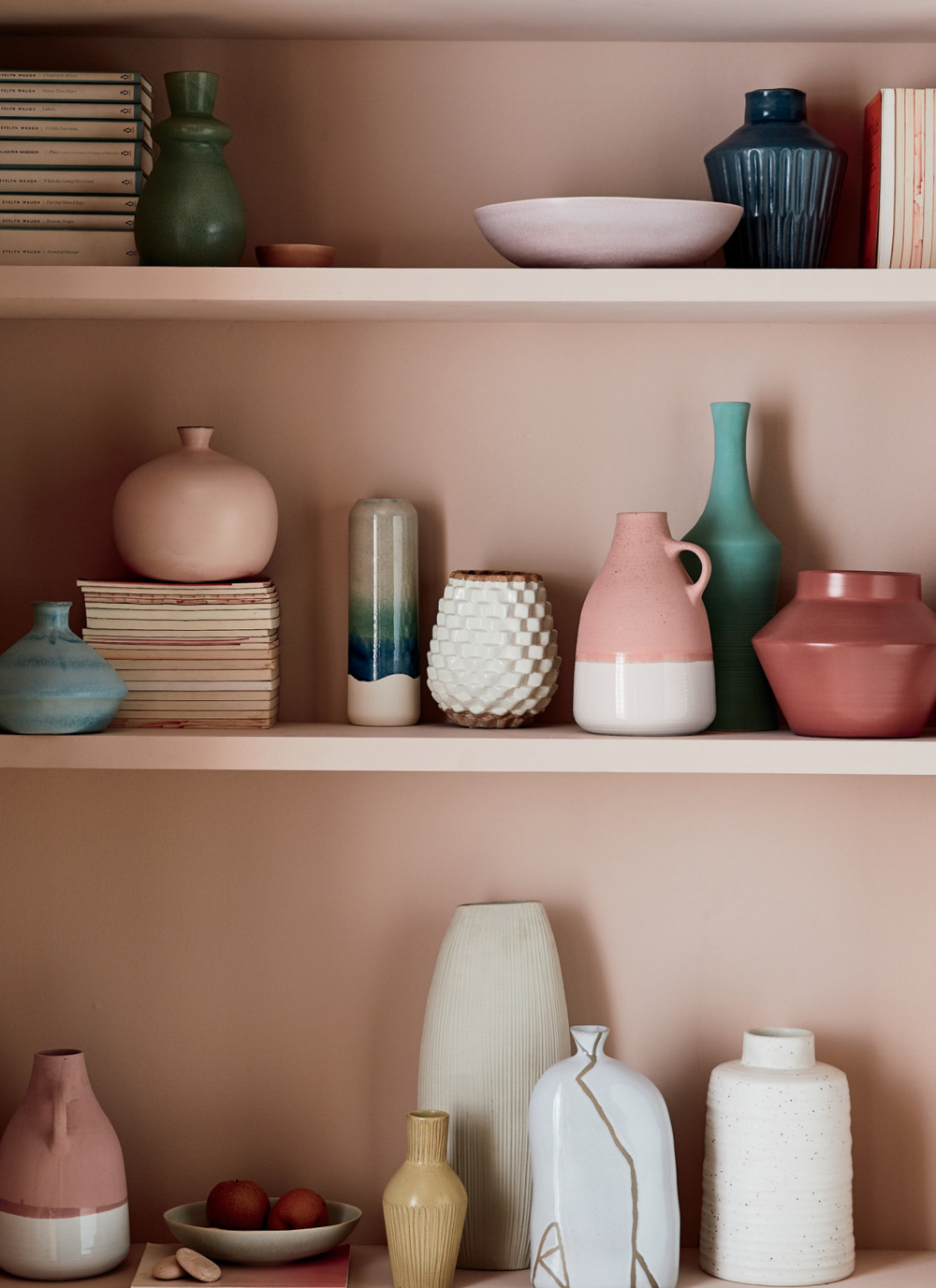A collection of vases against a dusty pink backdrop