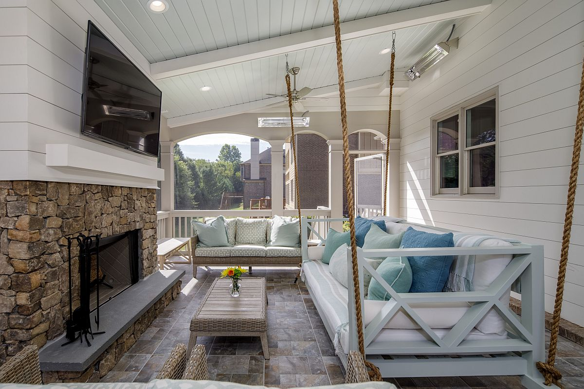 Accent pillows bring different shades of blue to the spacious and stylish porch