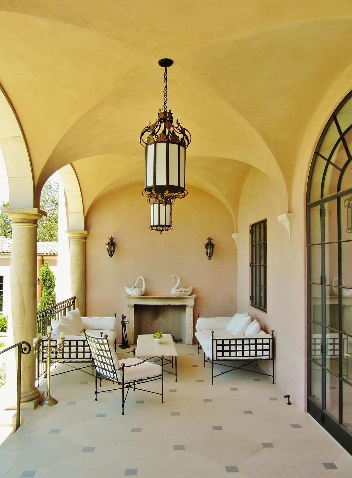 Arches, plastered walls and a warm yellow glow bring unmistakable Mediterranean vibe to this porch