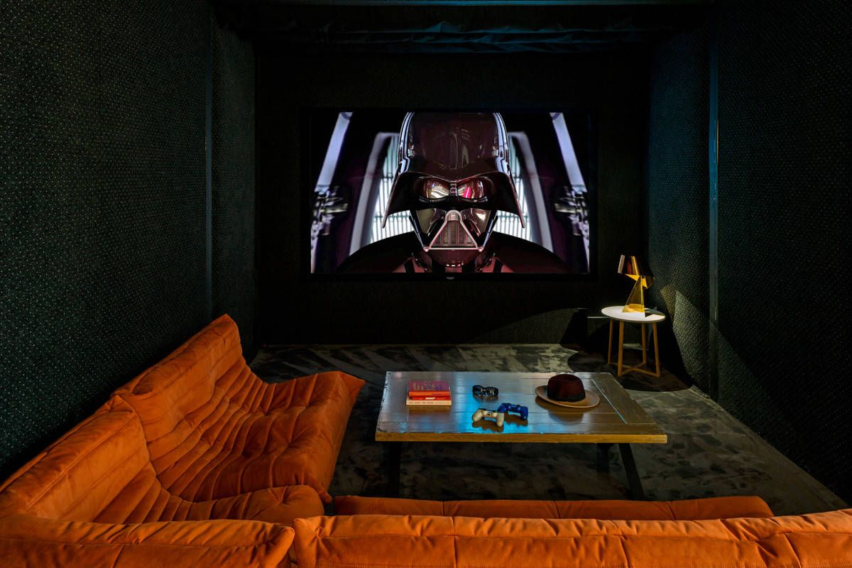 Black home theater in London with bright Togo Sofa and a projector