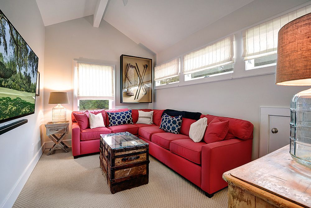 Bright red sectional maximizes sitting space in this tiny media room that is cheerful