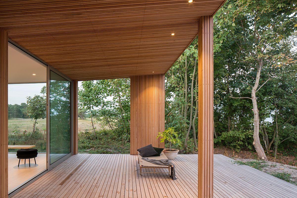 Covered deck of the summer house in Sweden offers lovely views of the Baltic