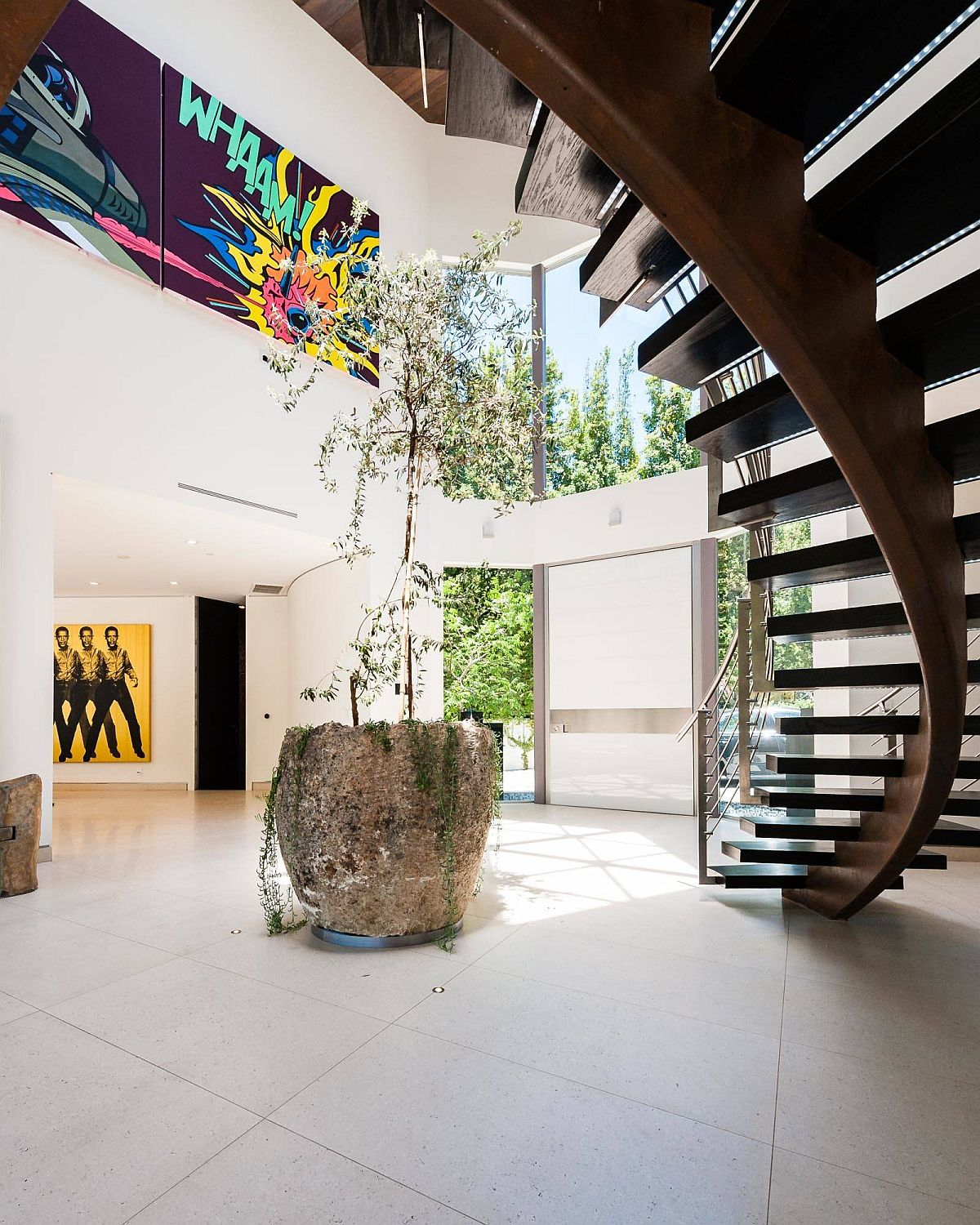 Fabulous indoor plant along with spiral staircase for the posh modern entry