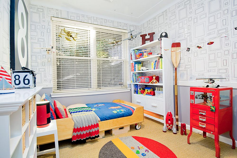 Fabulous kids' bedroom in white with a bed on wheels and plenty of red all around!