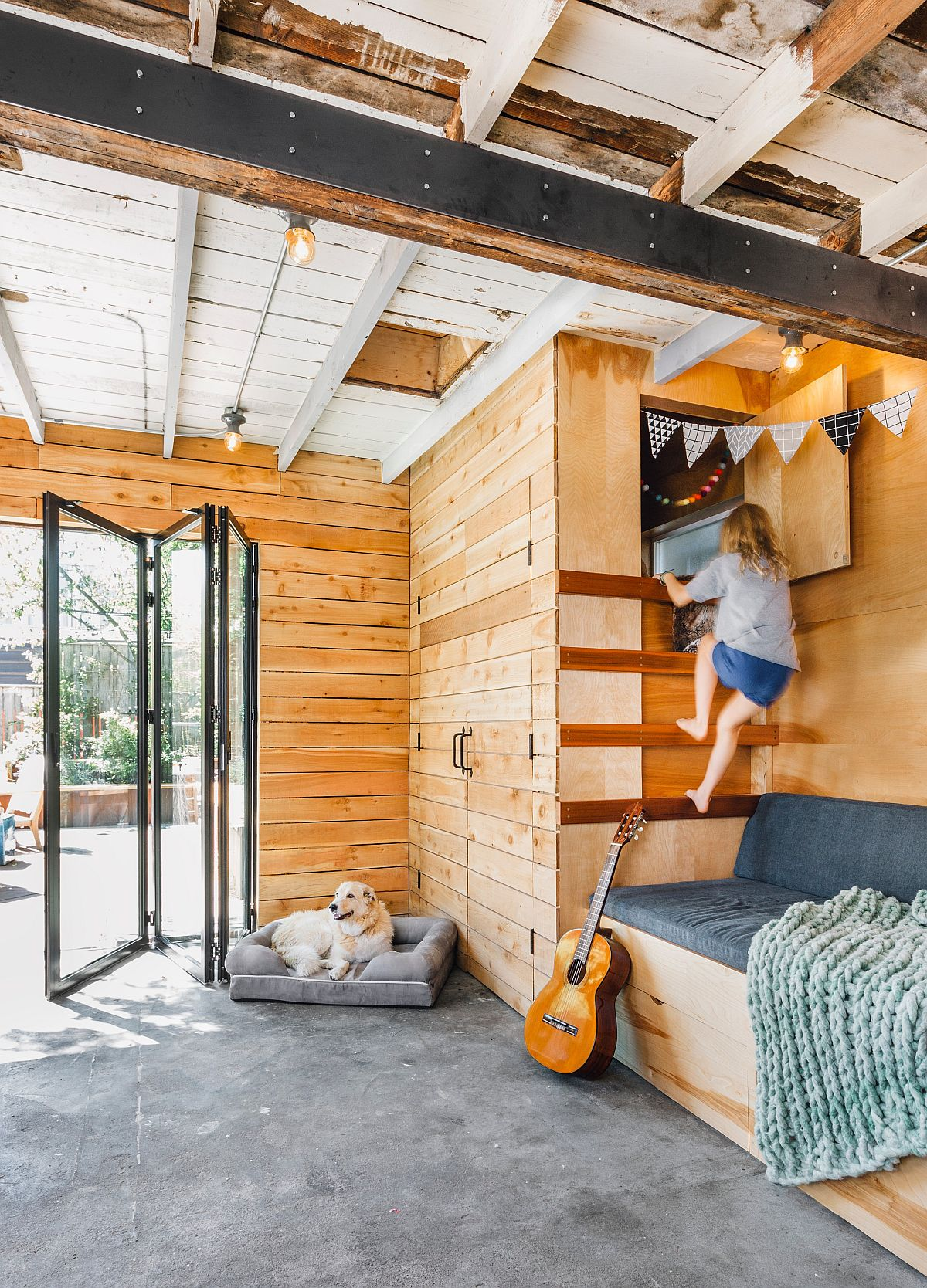 Farmhouse style kids' room with space-conscious bunk beds and concrete floor