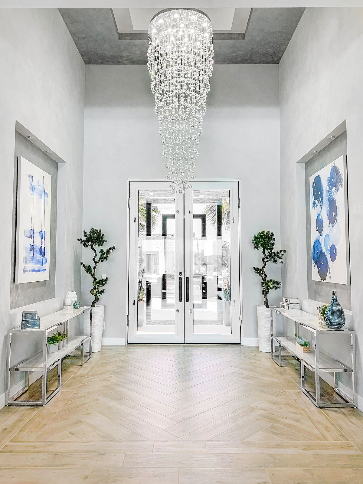 Gorgeous cascading chandelier lights up this large entry in white with greenery and pops of blue