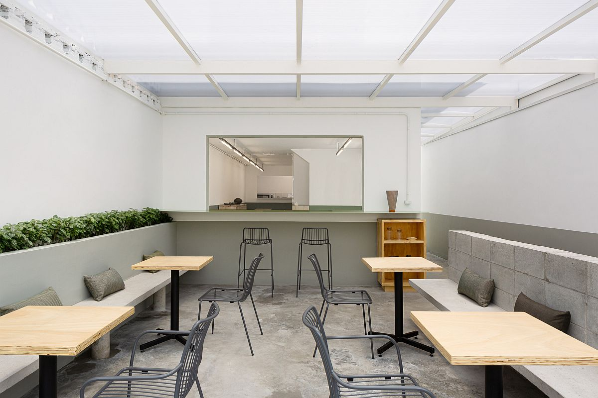 Gray and white are coupled with splashes of greenery and concrete inside the restaurant