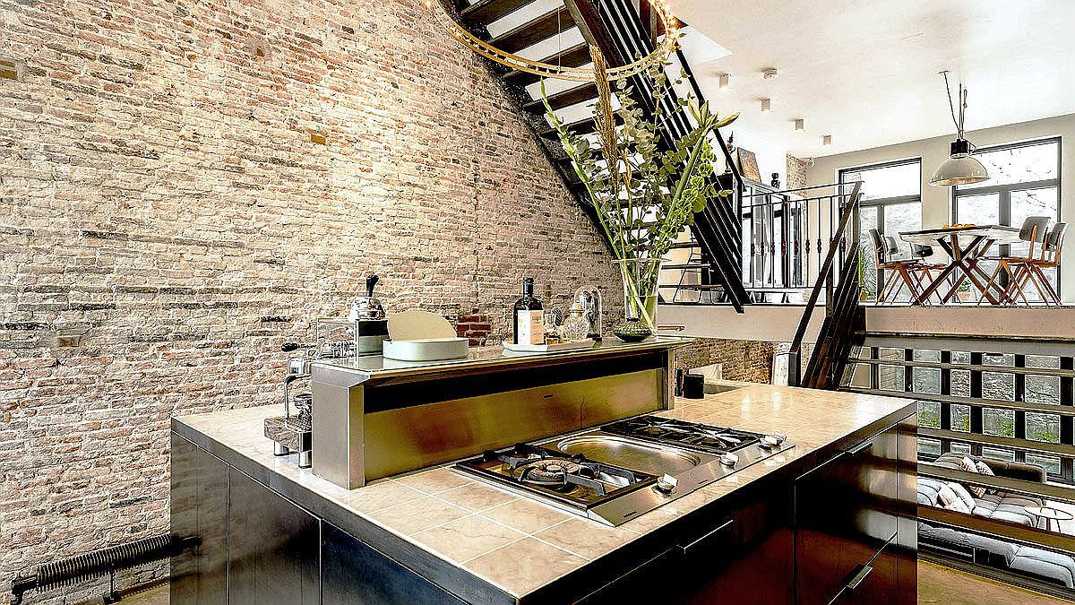 Metal staircase connects the split-level living area, kitchen and dining space