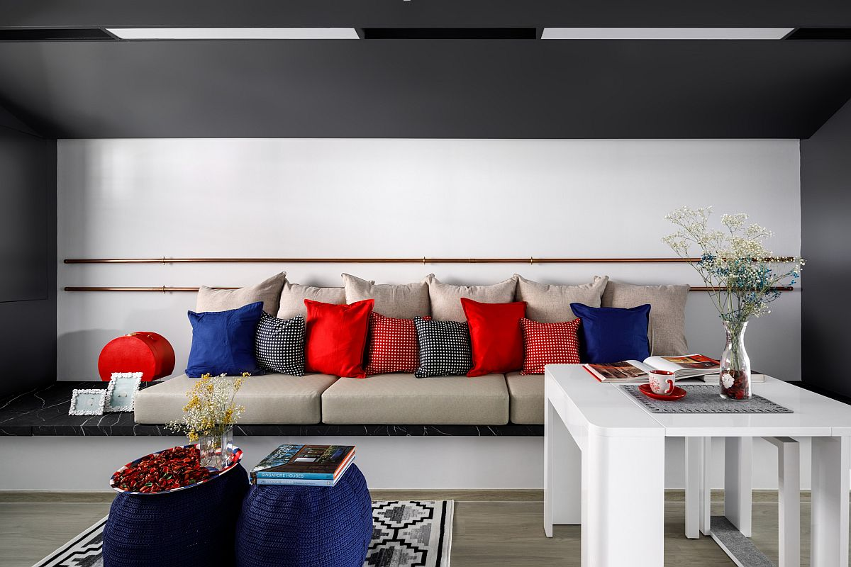 Minimal gray and white living area with accent pillows in multiple colors