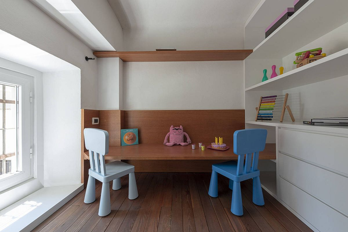 Minimal-play-area-inside-the-small-kids-bedroom-with-a-couple-of-chairs-wooden-shelves-and-ample-space-45356