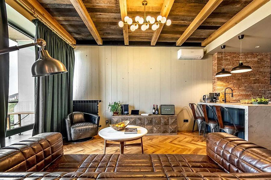 Modern industrial apartment living room with luxurious leather sofa and wooden ceiling and floors