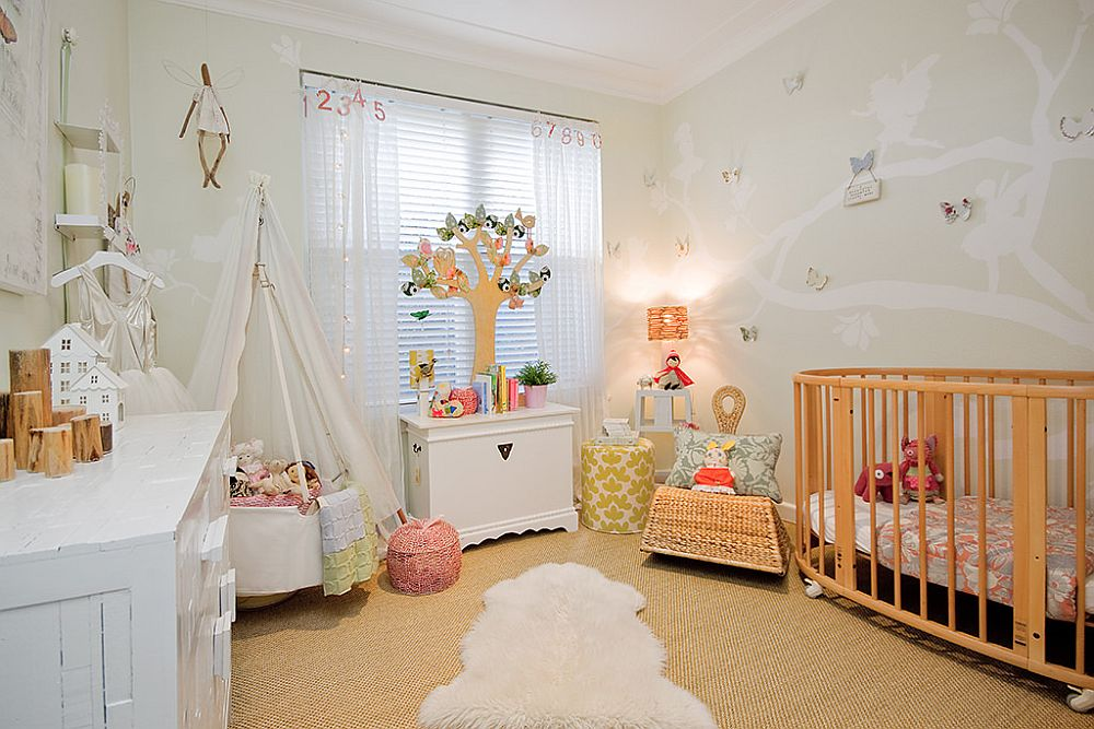 Nursery with custom wall decal, white walls and a beautiful playarea in the corner
