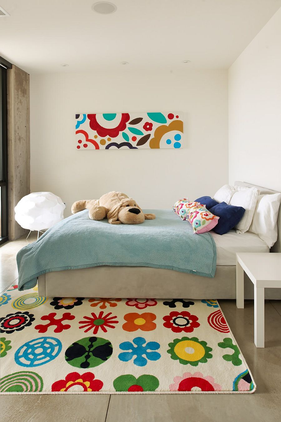 Rug, wall art piece and cushions bring bright floral pattern to this kids' room