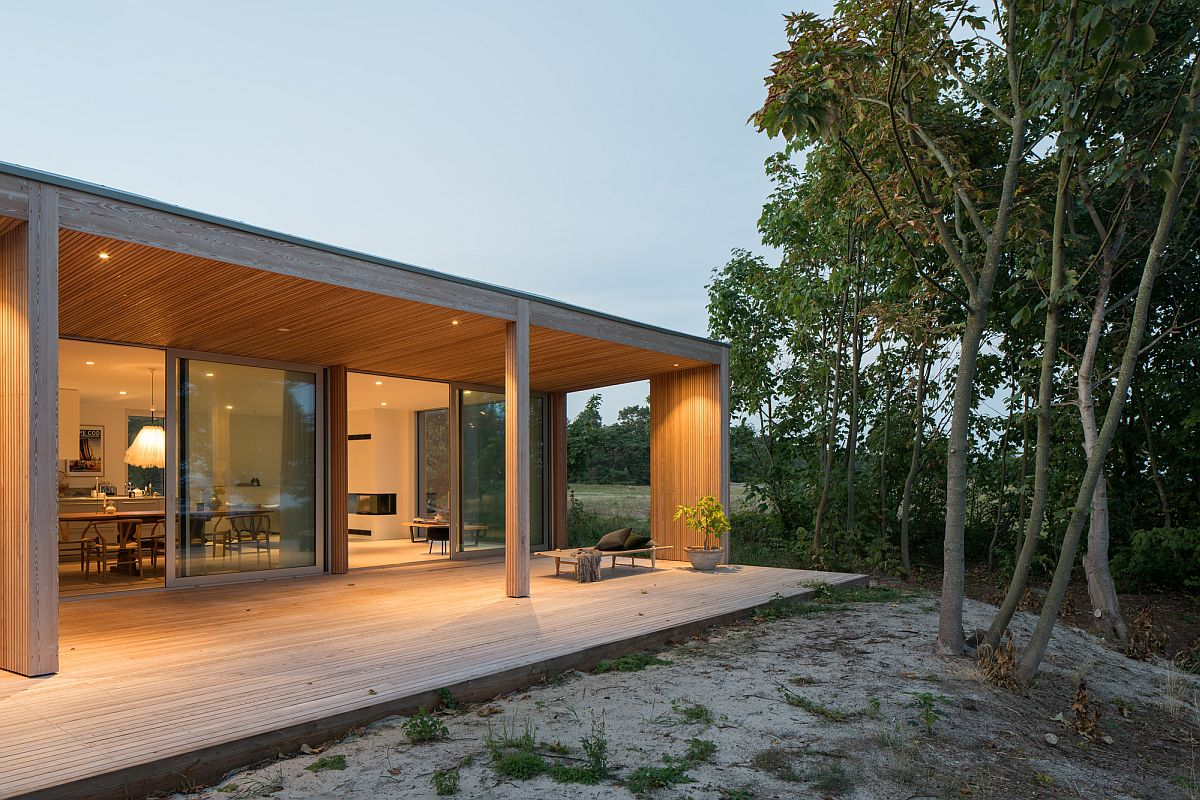 Sliding glass doors connect the interior of the summerhouse with the sweeping wooden deck