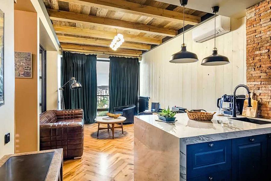 Small-modern-industrial-living-room-with-plush-leather-sofa-brick-walls-and-wooden-ceiling-53137