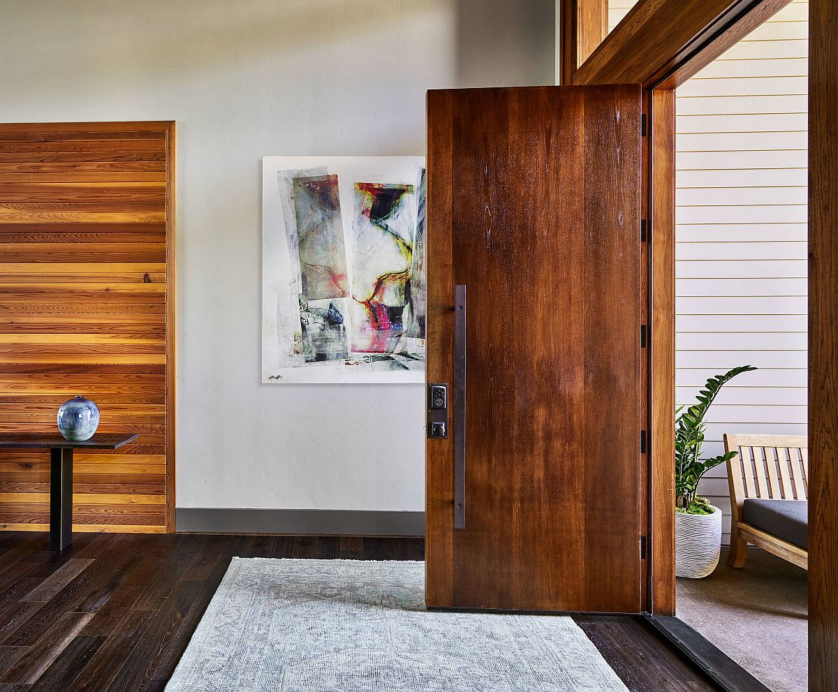 Smart wall art for the entry with wooden doors and polished finishes