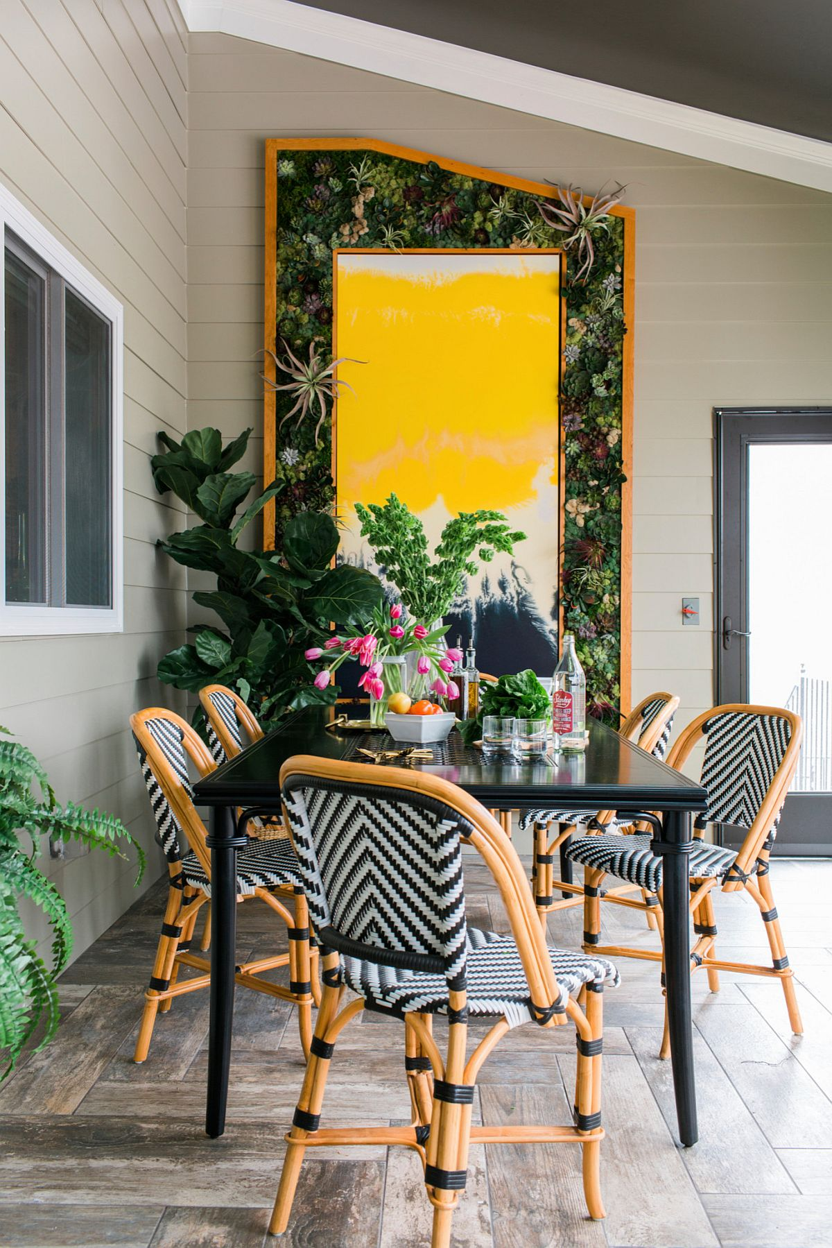 Stylish screened porch with gorgeous pops of yellow and green and chairs with chevron pattern