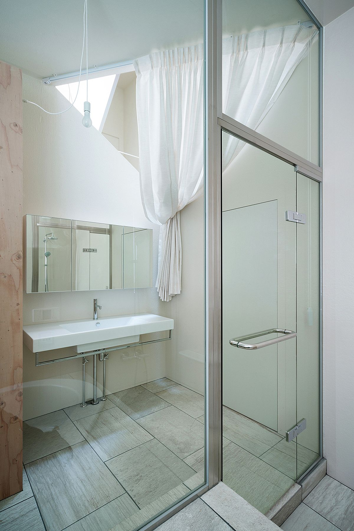 Triangular cut-out in the ceiling brings natural light into the small bathroom and shower area