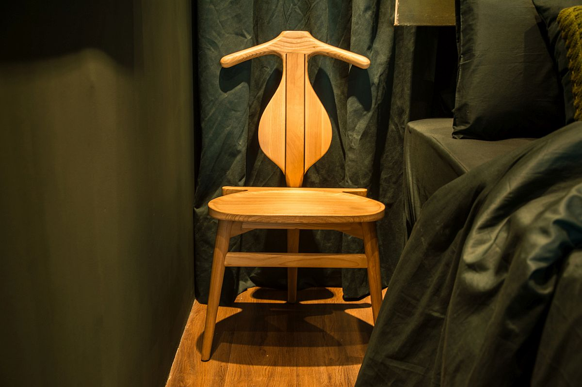 Valet Hans Wegner chair sits next to the bed inside the small and space-conscious bedroom