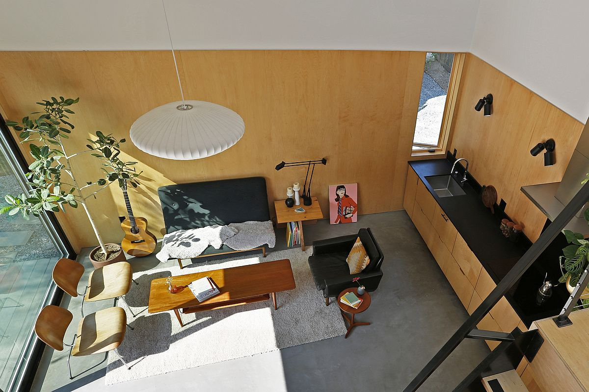 View of the small living area with wooden panel-covered walls from the loft level of the backyard house