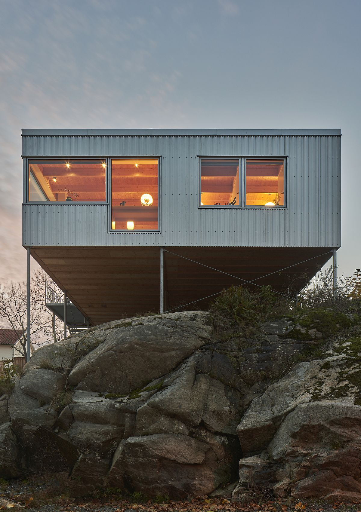 Warm lighting illuminates the interior of the house while adding to the facade
