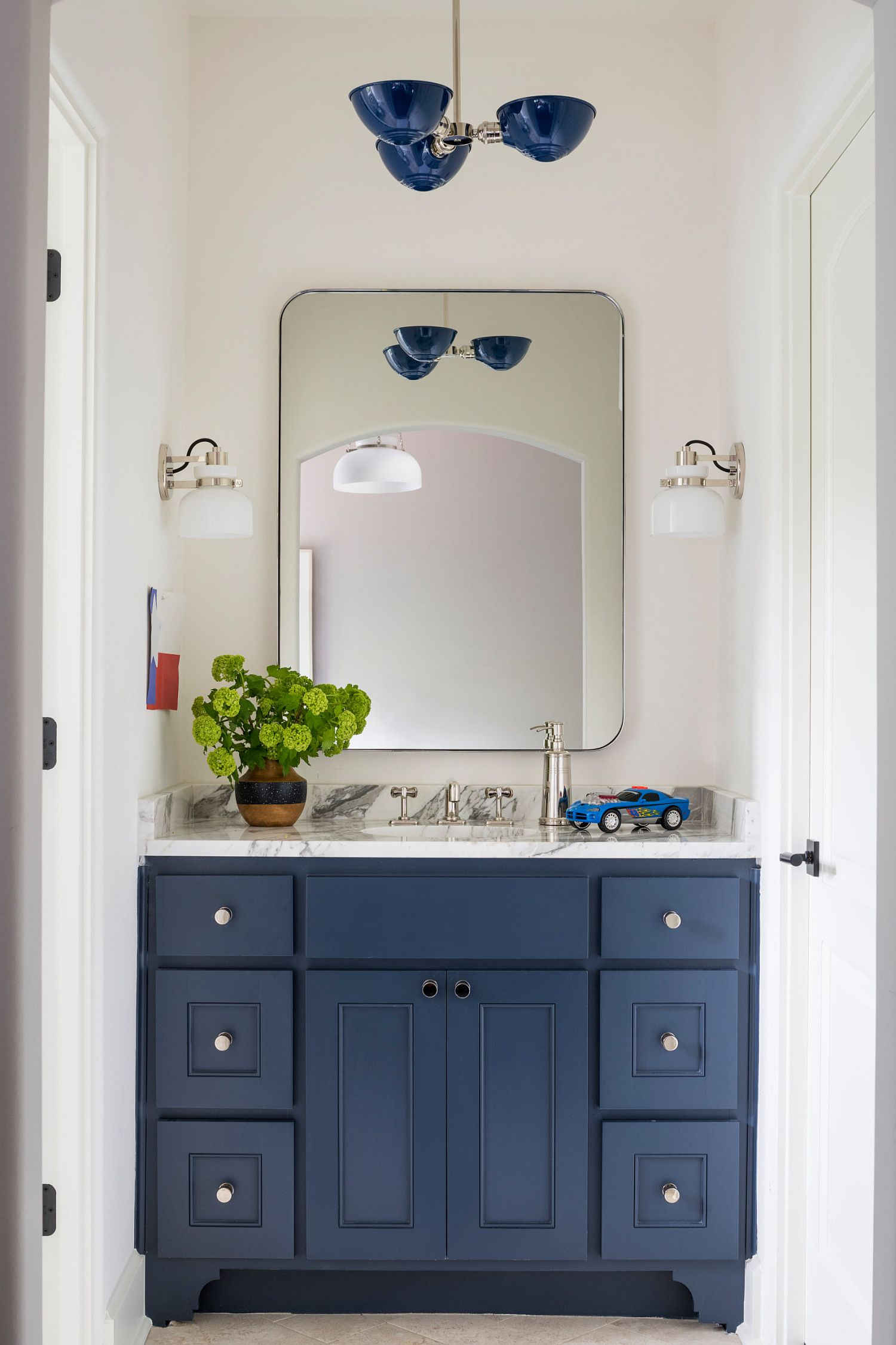 Adding a blue vanity to the white bathroom can instantly transform the ambiance inside the space
