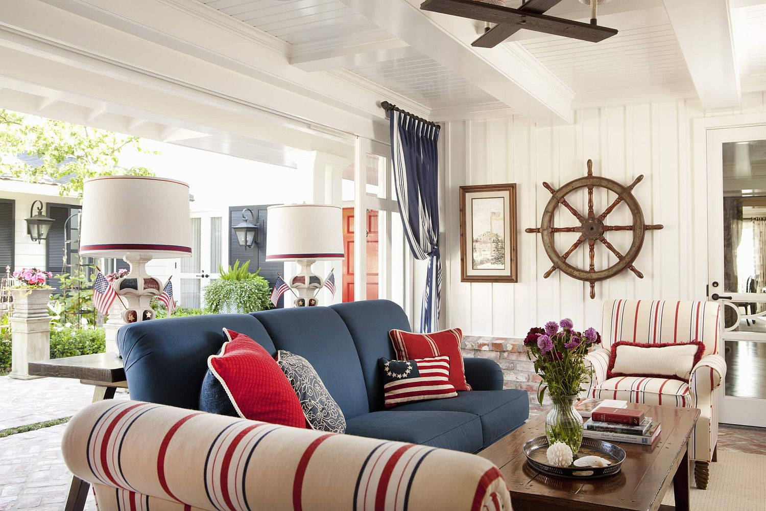 Beautiful-beach-style-porch-of-San-Deigo-home-with-bright-blue-couch-and-striped-chairs-in-cream-blue-and-red-31419