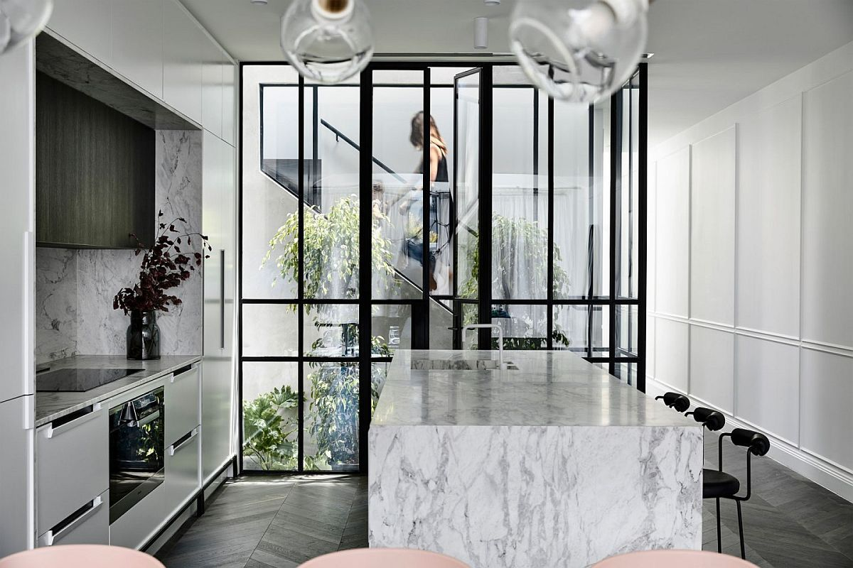 Beautiful white kitchen with dark framed glass wall in the backdrop and a delightful atrium