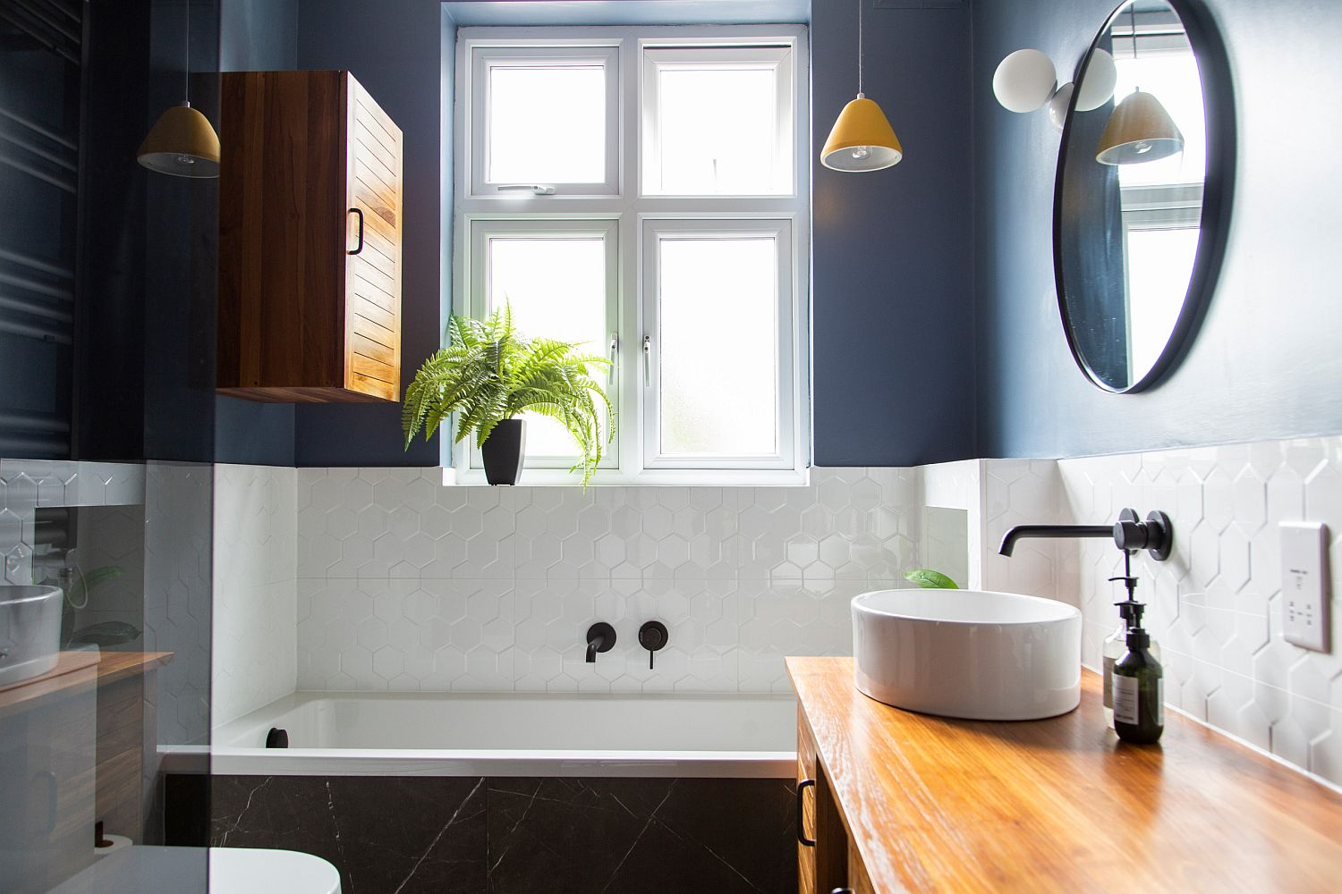 Blue walls, white tile and warm wooden vanity create a delightful balance of elements inside this London bathroom
