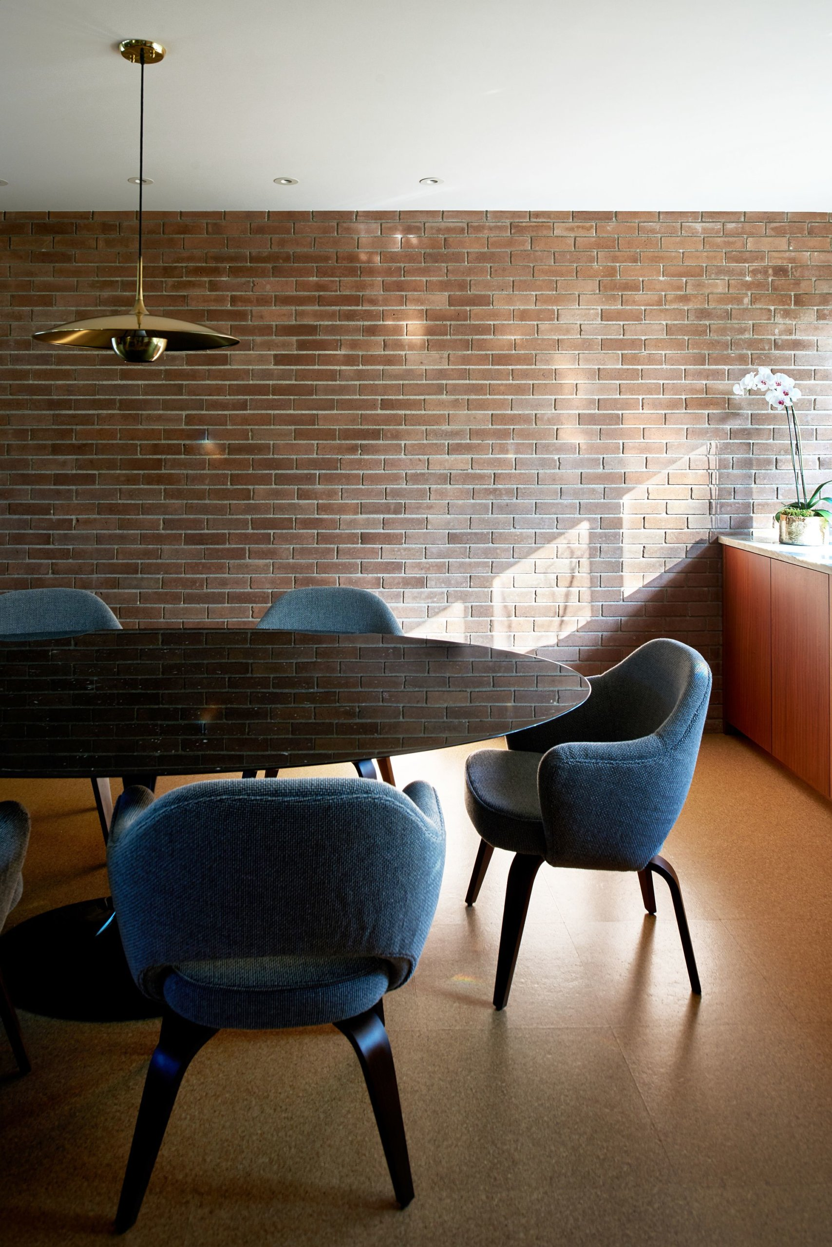 Brick walls give a modern-classic appeal to the light-filled dining room