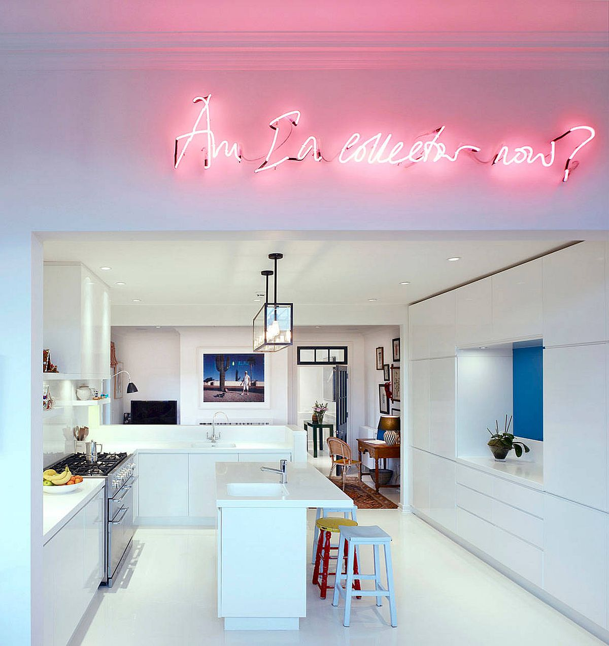 Bright neon sign illuminates the kitchen and living area inside this white Chelsea apartment