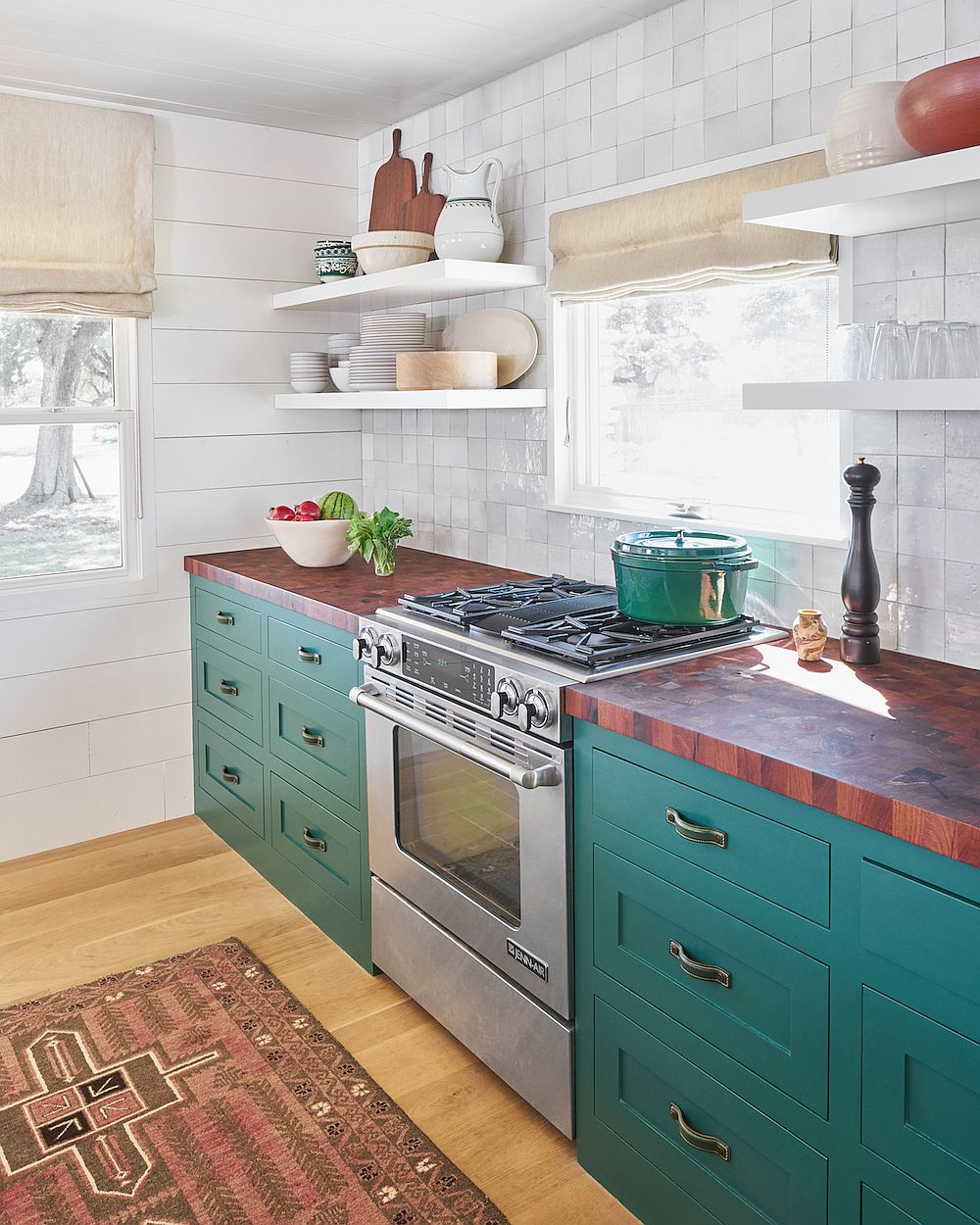 Butcher block kitchen coutertops combined with teal cabinets and white tiled backsplash