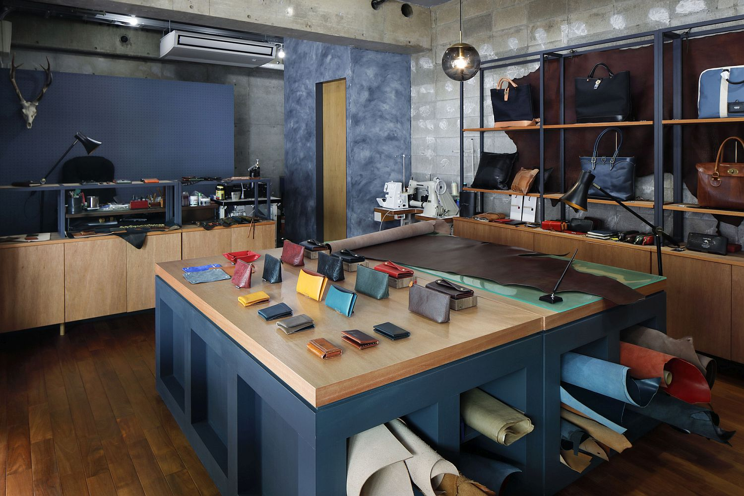 Central island of the shop in deep blue with a wooden countertop