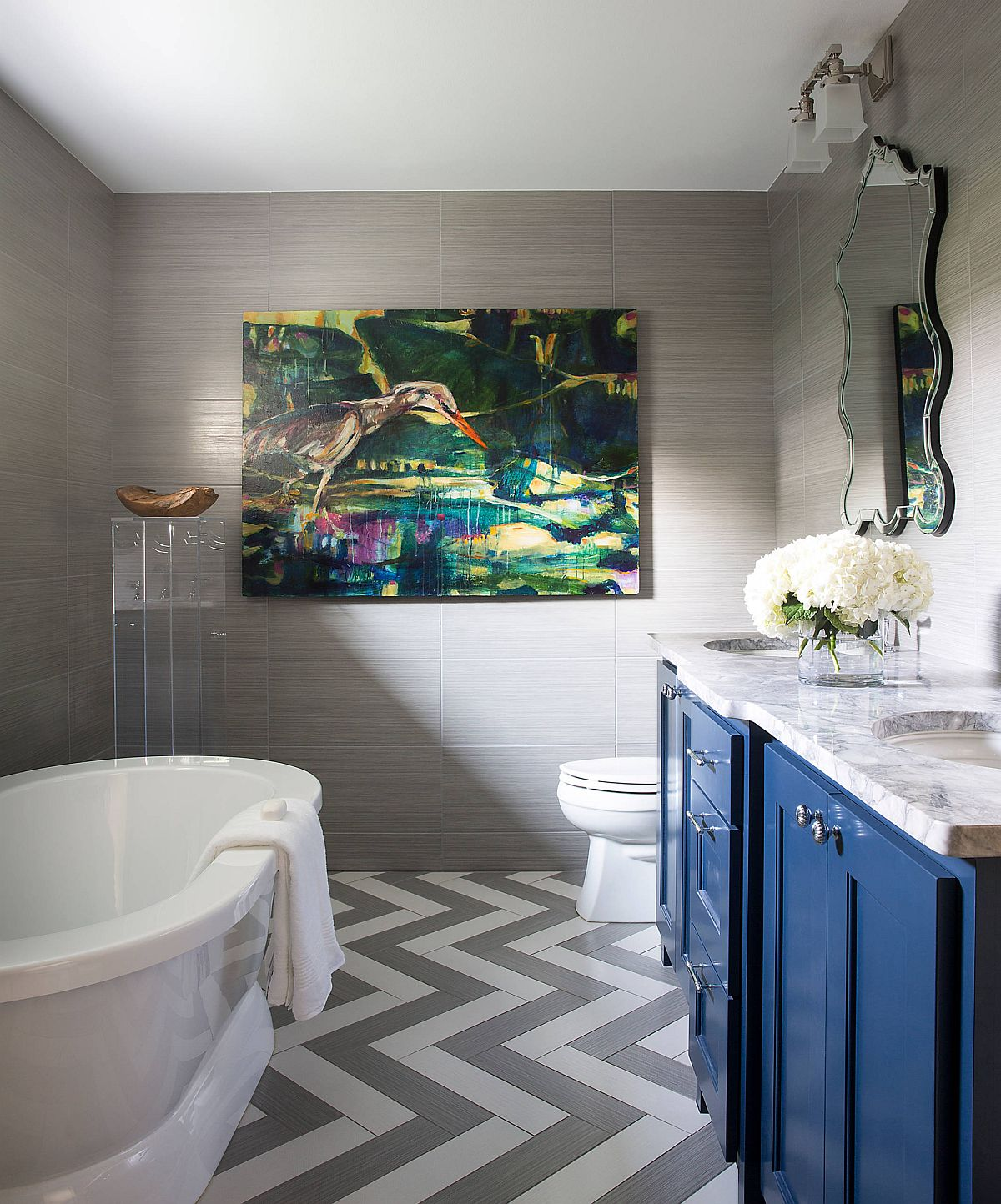 Chevron pattern floor in white and gray along wth blue vanity in the contemporary bathroom