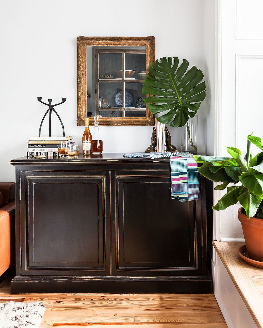Decorating the large wooden credenza in the living room with a touch of greenery