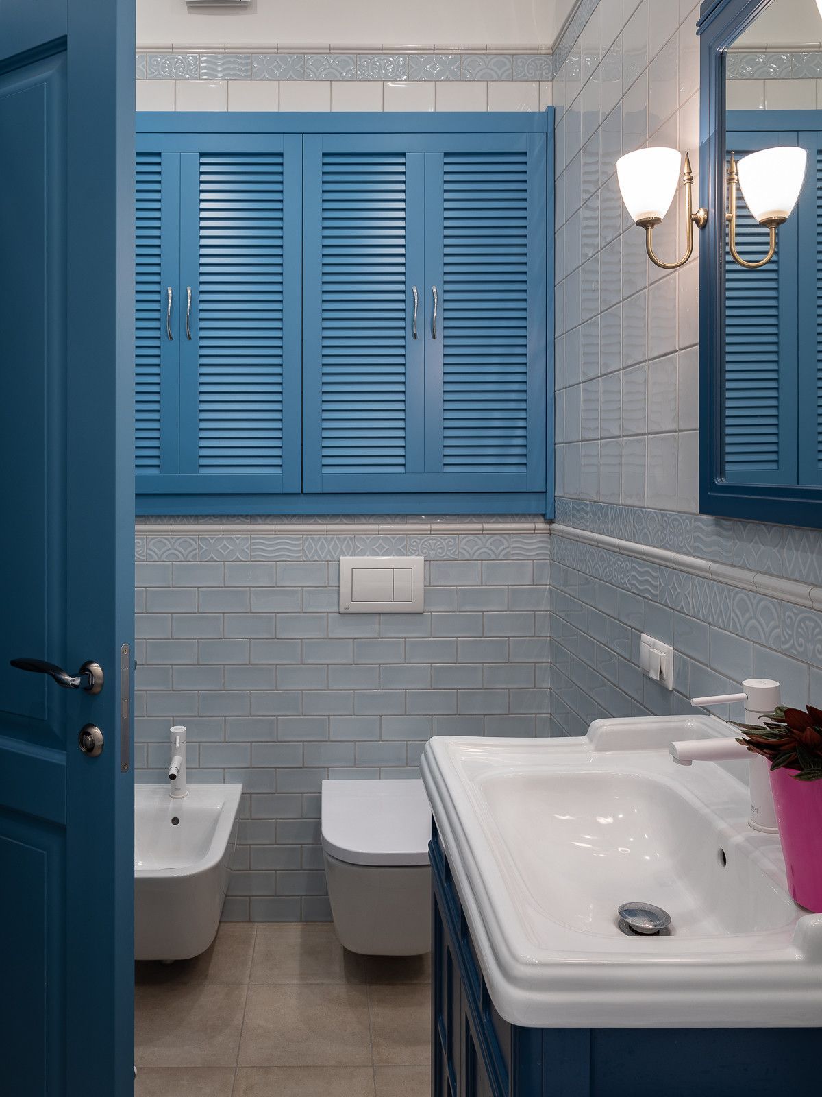 Door, window shutters and vanity bring blue to this small traditional bathroom