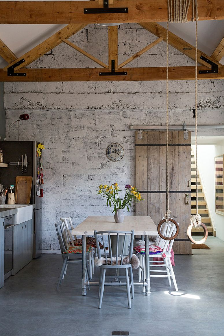 Double-height-dining-room-of-the-classic-home-with-whitewashed-brick-wall-backdrop-16002