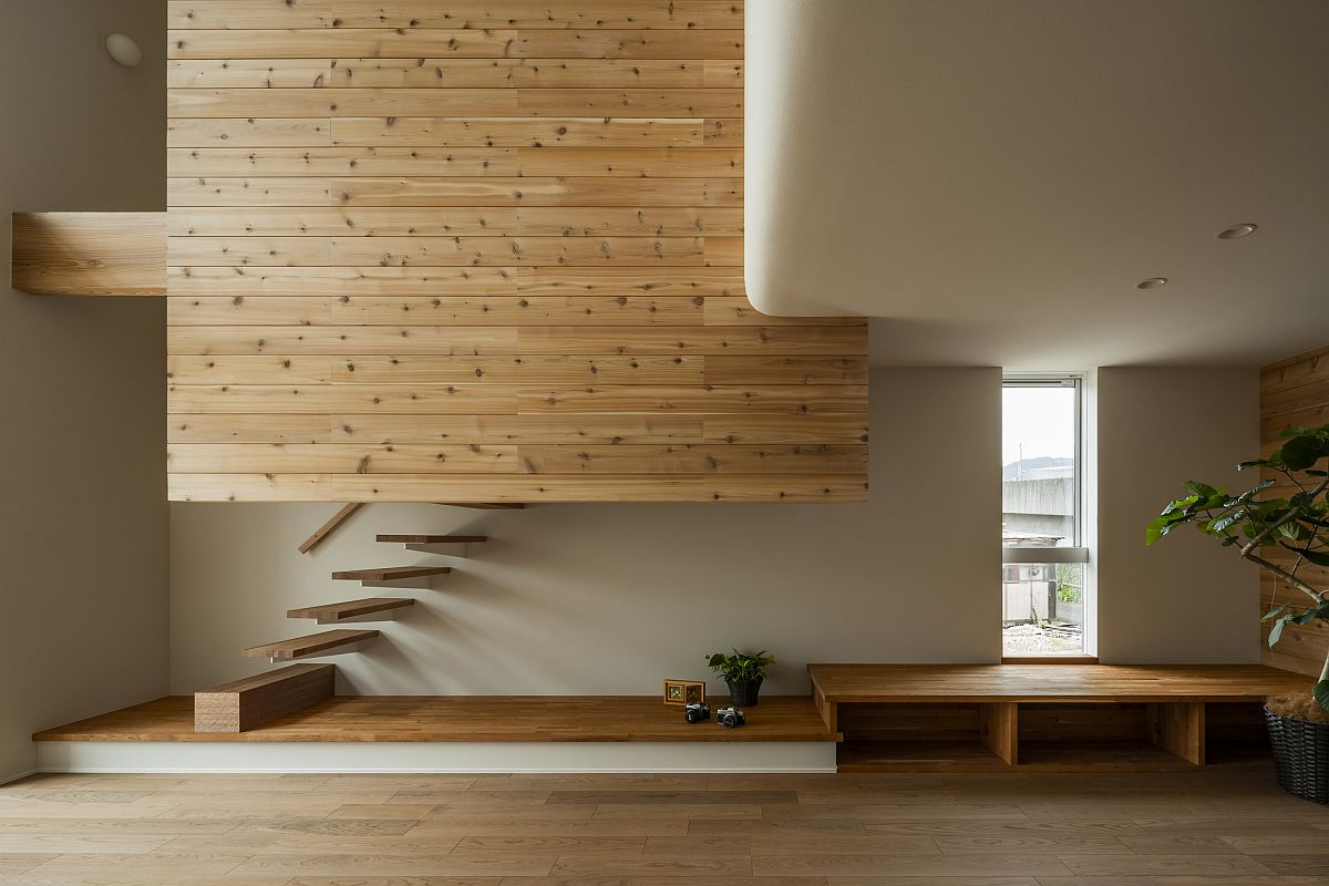 Double-height living area of the Japanese home with floating staircase, wooden walls and ample natural light