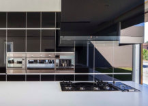 Glossy-black-backdrop-and-sainless-steel-appliances-stand-in-contrast-to-the-white-and-wood-in-the-kitchen-22635-217x155