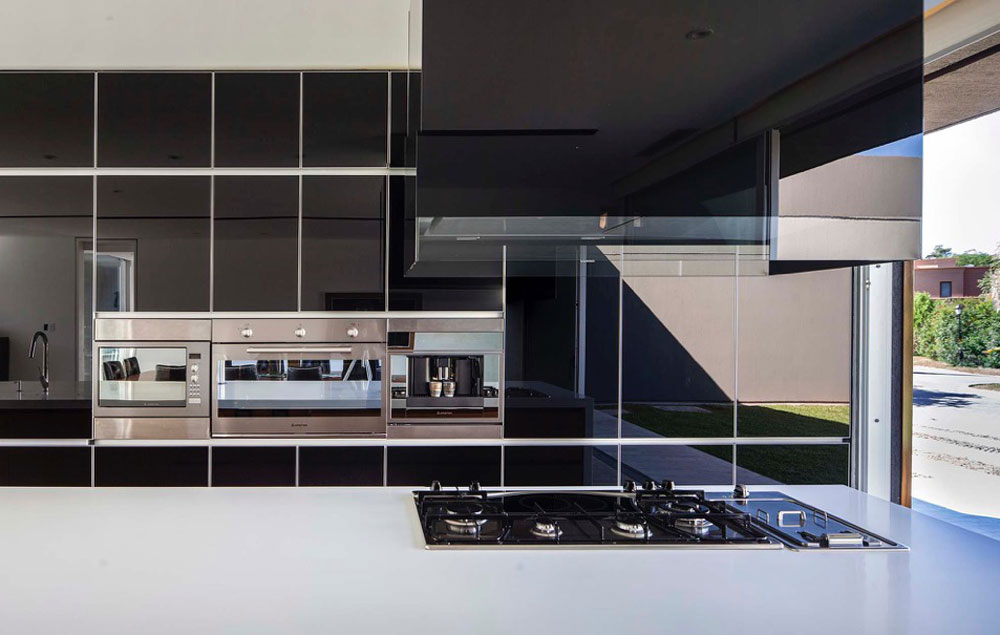 Glossy-black-backdrop-and-sainless-steel-appliances-stand-in-contrast-to-the-white-and-wood-in-the-kitchen-22635