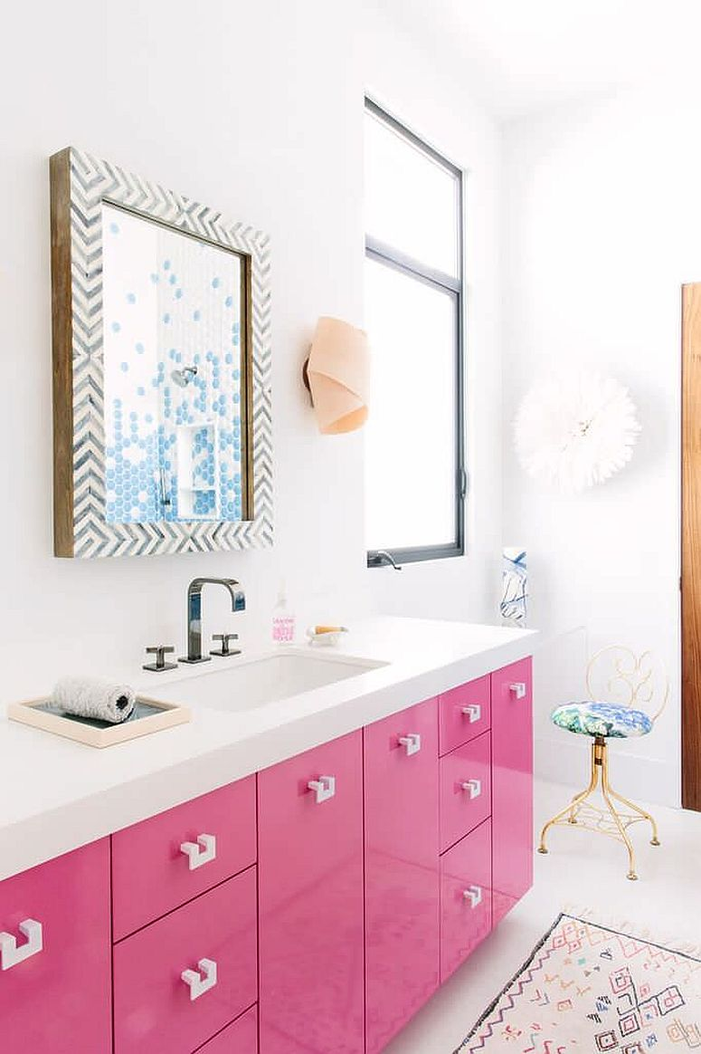 Gorgeous pink vanity with white countertop and a bright, lacquered finish