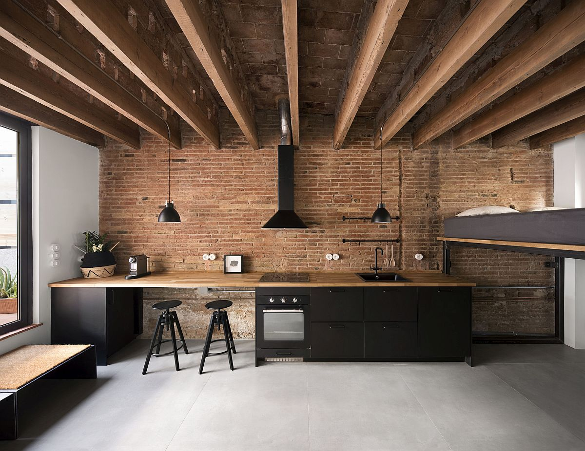 Gorgeous single-wall kitchen with brick wall backdrop inside the small attic apartment
