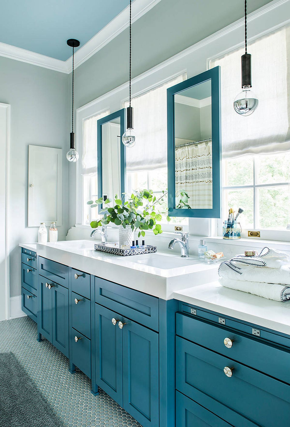 Gray bathroom with blue cabinets, mirror frames and ceiling