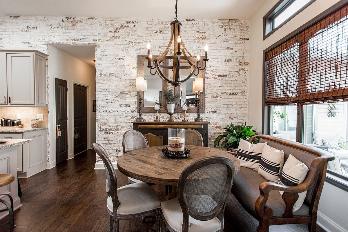 Imperfections of the whitewashed brick wall accentuate the beauty of this dining room